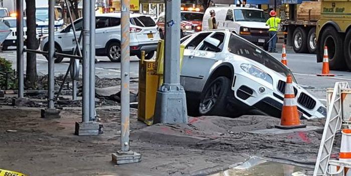 Bmw x5 تسقط في حفرة في نيويورك بعد انفجار أنبوب مياه coobra.net